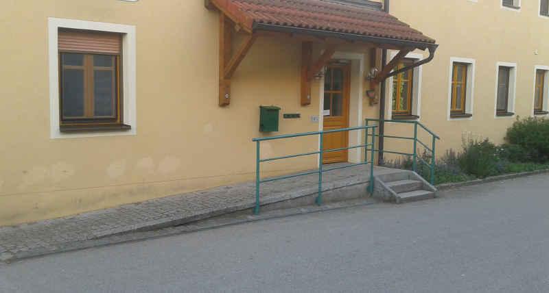 Hauseingang mit_Rampe, die Steigung der Straße wird mit genutzt.