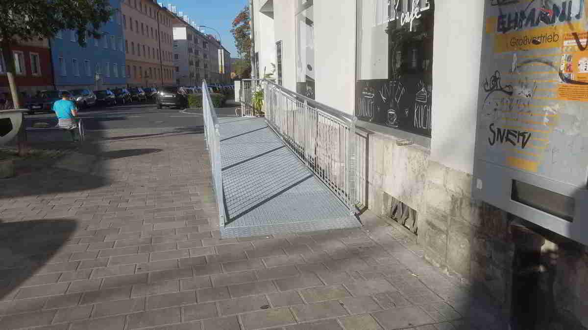 Rampe aus Edelstahl vor Cafe-Eingang.
