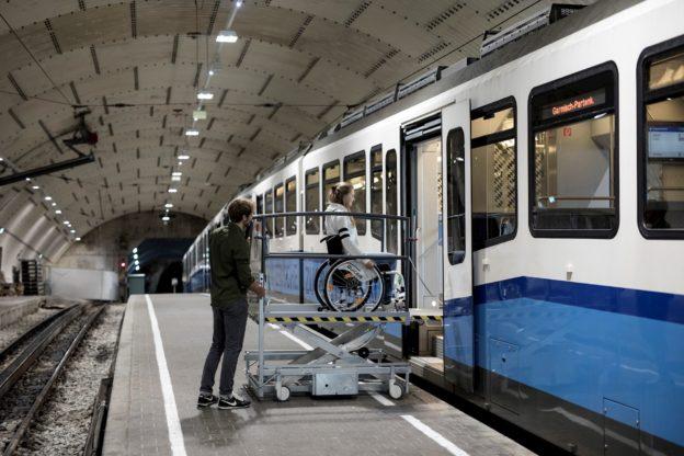 Rollstuhlfahrerin auf einer mobilen Hebebühne.