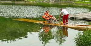 Ein Badegast wird auf einem Baderollstuhl die Holzrampe heruntergefahren.