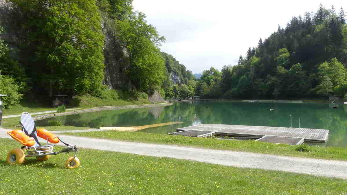 Der Luegsteinsee mit einem Baderollstuhl und der Rampe, die in das Wasser führt.